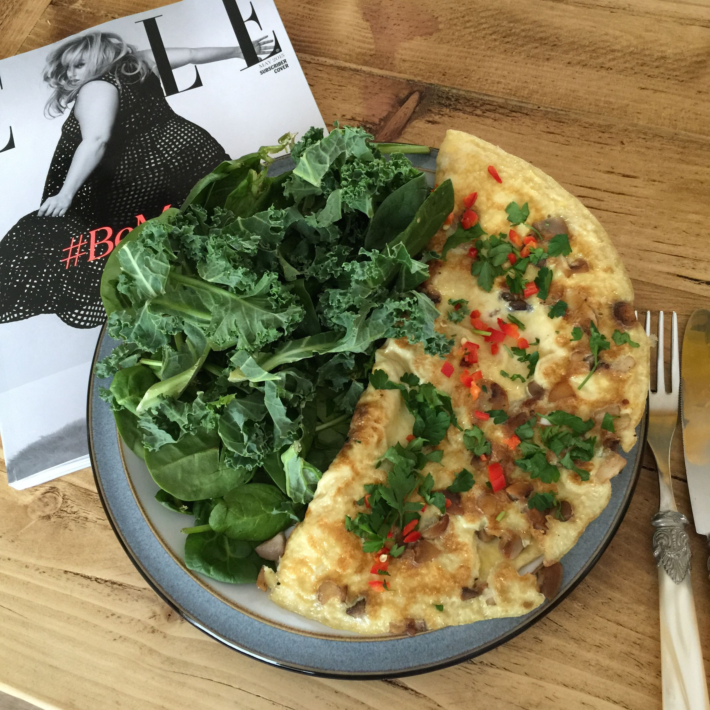 Mushroom omelette with added fresh chilli and parsley, served with raw spinach, kale and ELLE magazine. Following The Body Coach 90 Day SSS plan