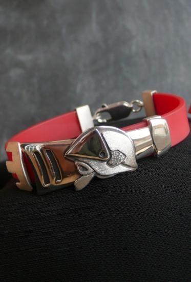 Pulsera con casco de bombero y lanza por debajo en plata de ley y caucho rojo de 1 cm. Se puede cambiar el caucho por otro color u material como cuero. Hecha a mano.