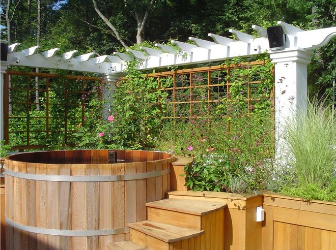 Floral screen. Trellises on two sides of this wooden hot tub ...