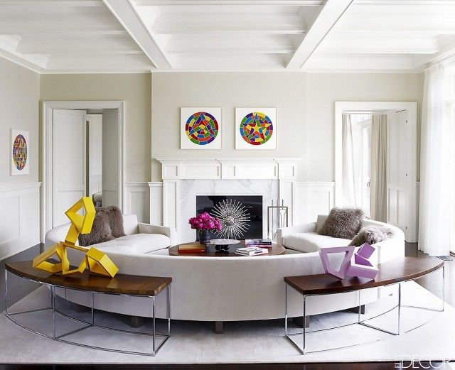 Elegant living space with a fireplace as the focal point of living room with a rounded sofa