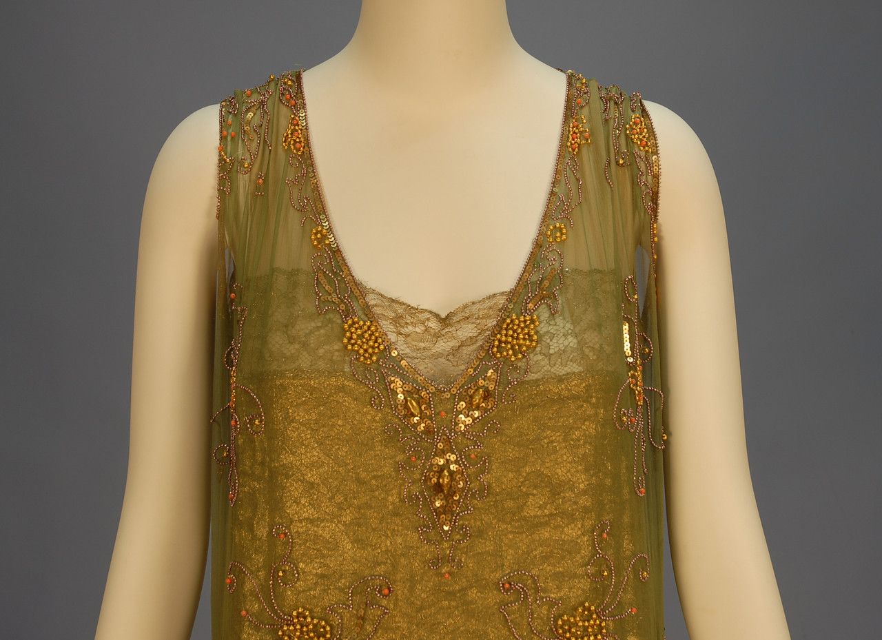 BEADED CHIFFON and GOLD LAME FLAPPER DRESS, 1920's. Sleeveless sage chiffon with V-neck and back with T strap, decorated in a floral pattern of gold beads and sequins studded with coral beads, the skirt having four heavily beaded lame swags. Lame under dress trimmed in gold metallic lace with nude chiffon straps. Detail