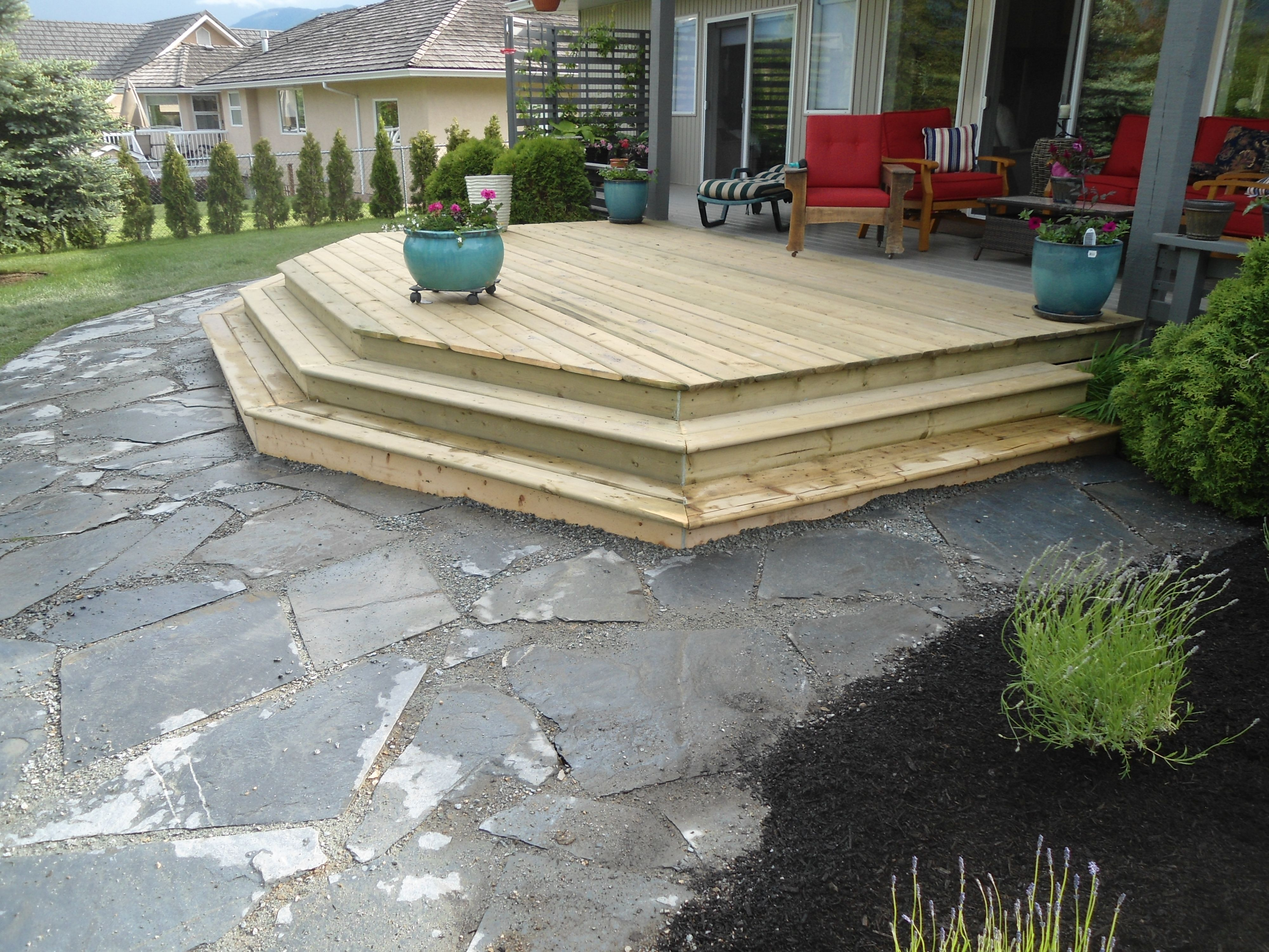 with a new deck and flagstone patio leading to a small pond and