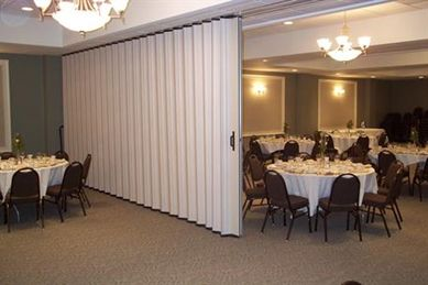 Soundproof accordion-type side folding panels suspend from ...