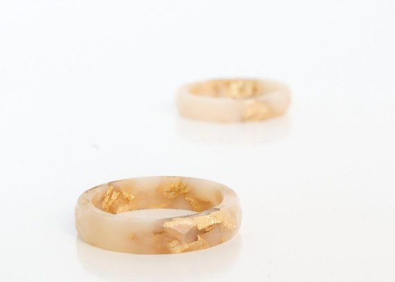 This shiny round eco resin ring is an opaque neutral peach colour featuring gold flakes. This ring style is very thin and subtle and looks great
