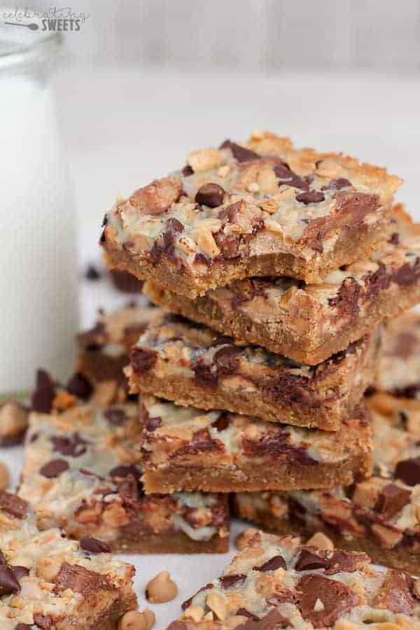 Peanut Butter Cup Magic Cookie Bars - Peanut butter cookie crust, chocolate chips, peanut butter chips, peanut butters cups, and salted peanuts make up these gooey, addicting bars.
