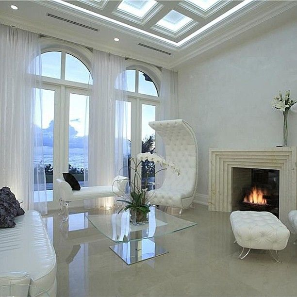 Art Deco-esque fireplace with quilted, crescent-shaped lounge chairs overlooking dramatic ocean views.