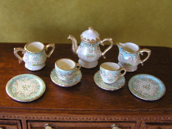 A hand-painted twelfth scale tea set. Painted by myself on British made metal miniatures. A very delicate pale green on a cream background, with gold and floral decoration. The tea pot measures 1.75cm high. The lid is removable. This is a collectors item and is not suitable for children.