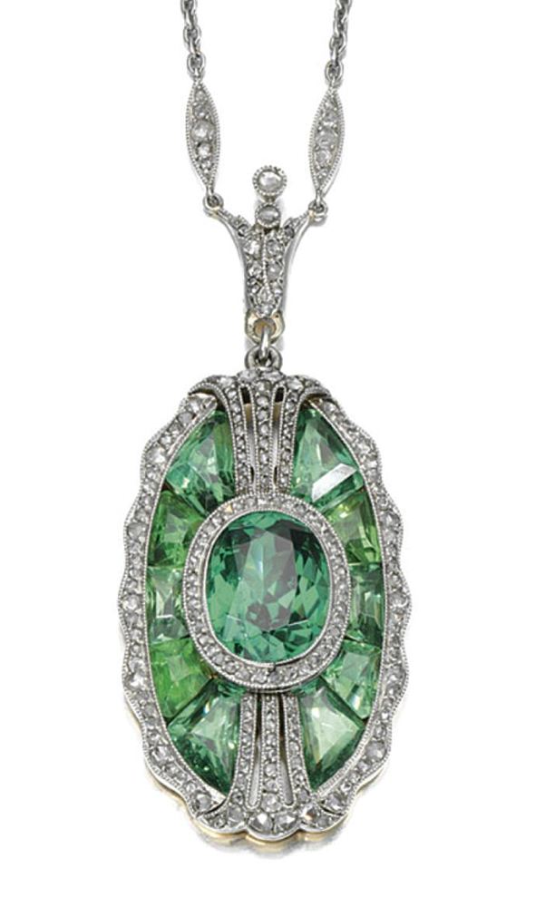 DEMANTOID GARNET AND DIAMOND PENDANT, CIRCA 1910, COMPOSITE. Set with an oval demantoid garnet within a surround of calibré-cut similar stones, the borders set with rose-cut diamonds, to a later trace link chain, length approximately 400mm, signed Tiffany & Co.