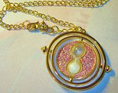 Harry Potter a Time Turner in Hand Necklace , Silver & Gold with Personalized Parchment Note (silver sparkly). $39.99, via Etsy.