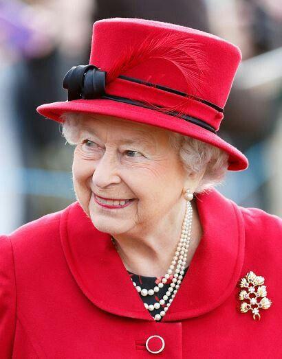 Queen Elizabeth II in a red hat by Angela Kelly