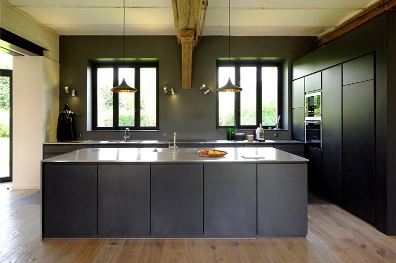 La cuisine et la zone repas avec les portes coulissantes en position ouverte dans un loft for Cuisine noir mat