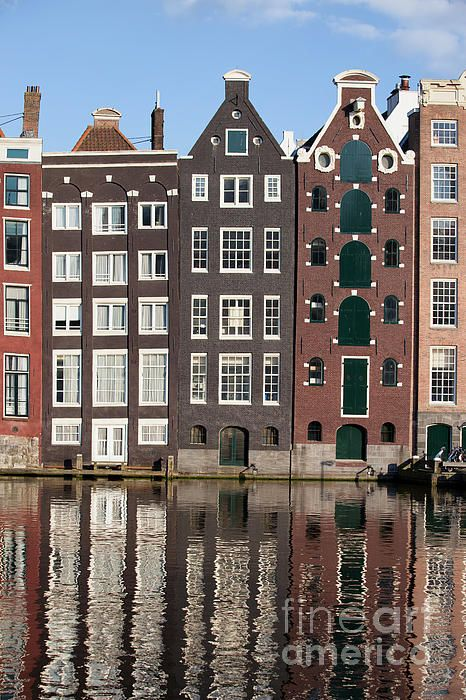 Traditional Dutch style row houses on a canal with reflections on water in Amsterdam, Holland, Netherlands.