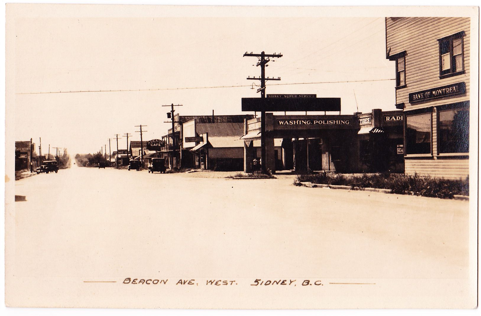 Photo postcard of Beacon Avenue at Third Street. Bank of Montreal is now the 3rd Street Cafe and Sidney Super Service is now a Royal Bank. Gowen, Sutton circa 1933-1937.