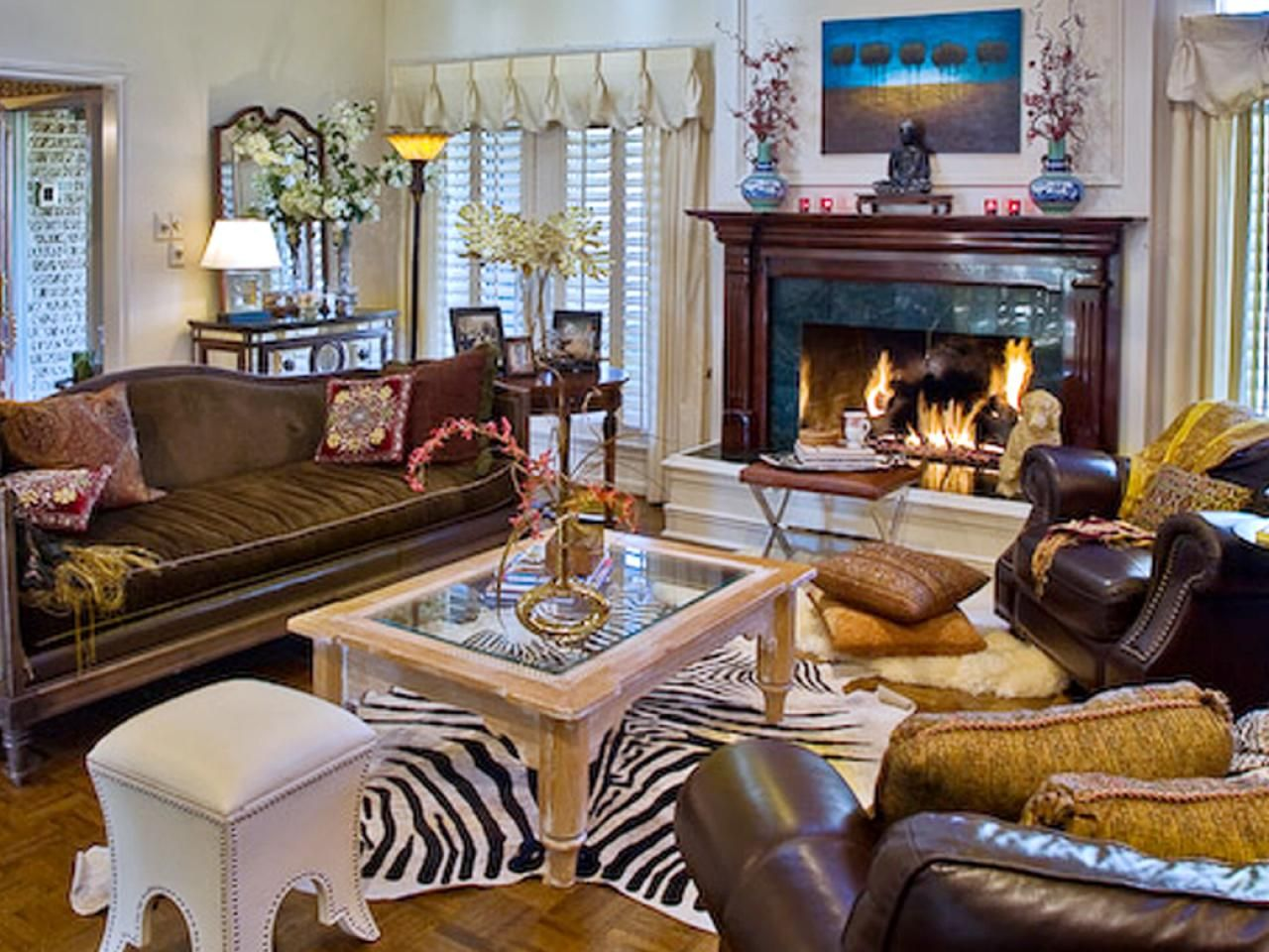 This eclectic living room centers around a zebra-print rug. It is ...