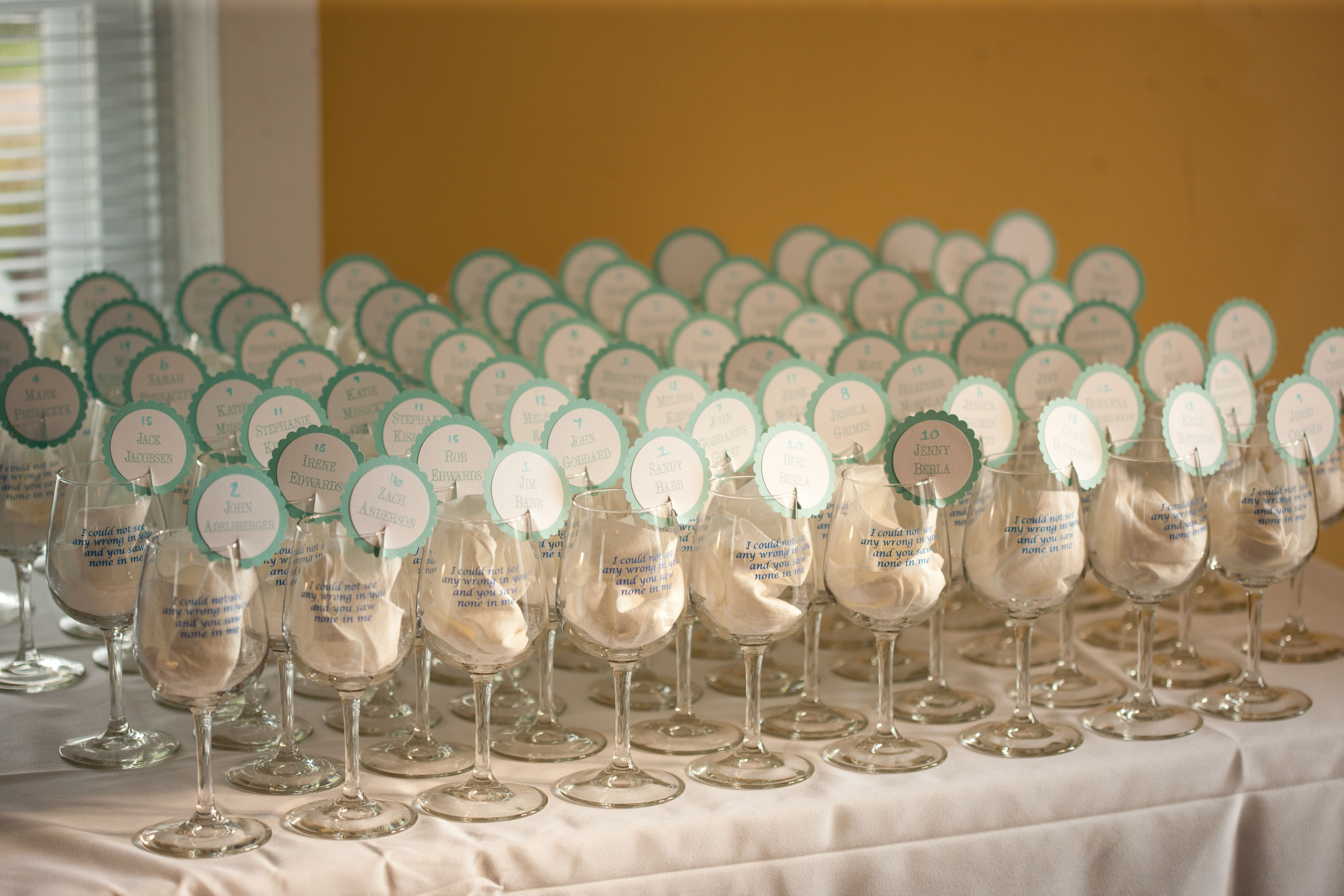 Wedding Favors Wine Glasses With Lyric Printed On Them And Place Card Sitting Rim