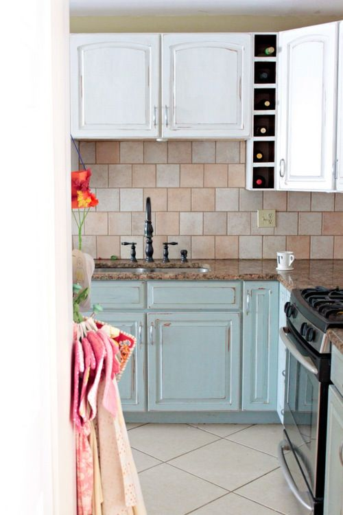 charming! Look at the little wine cubbies, and the use of blue and white cabinets with granite and stone...