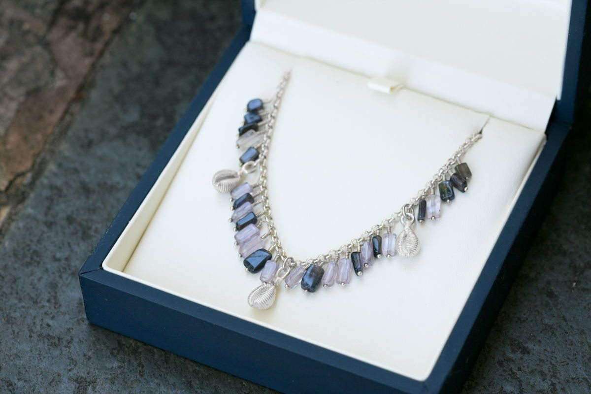 @alohikaijewelry posted to Instagram: So my sister and I were going to give a gift to an aunt. We chose this cowry, iolite and amethyst necklace (cause we like her) Cleaned, boxed and ready to go, when my mom says no, its a bad choice, better give her earrings. Sigh. 🤣 So we have this lovely one of a kind necklace available! DM me if you like it . #madeofocean #nakedhawaii #sealovers #oceanminded #saltwatertherapy #oceanlove #lethawaiihappen #oceanlife #staysalty #slowfashionmovement #oce