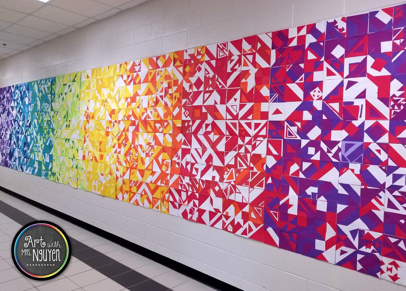 Back to School Collaborative Mural 2017 is part of Collaborative art, Art education elementary, Collaborative mural, Collaborative art projects, Elementary art classroom, Group art projects - 2 months before seeing some of my rotations, so this was a welcomed change! So during the first 8 days of school I introduced myself, went over my classroom rules, some procedures, and assigned seats for 48 separate classes! After all the boring introductory stuff, I also had my 2nd5th grade students work on a collaborative mural project  This lesson comes from Don at Shine Brite Zamorano! We started by looking at the artist Libs Elliot  I showed students some examples of her work and then we briefly talked about how she was able to simultaneously create a sense of unity and variety in her artwork  After looking at some of her pieces, we landed on a slide which showed the GORGEOUS mural that Don had his students make, then I explained what we were going to do! Students were instructed to create a square patch with construction paper, that would be added to a nearly schoolwide collaborative mural project inspired by the work of Libs Elliot  At each of my tables I put a basket filled with 6 x6  squares, large triangles (cut from 6 x6  squares), and 3 x3  squares in a number of different colors (colors were switched out for each rotation)  Students were told they needed one large square, one large triangle, and two small squares (which could be cut into smaller triangles)  then the rest was up to them! I used the following schedule for my color rotations Rotation 1 Scarlet, Magenta, White Rotation 2 Red, Scarlet, Orange (some), White Rotation 3 Orange, Gold, Red (some), White Rotation 4 Gold, Yellow, Light Yellow, Orange (some), White Rotation 5 Light Yellow, Hot Lime, Holiday Green (some), White Rotation 6 Hot Lime, Holiday Green, Turquoise, White Rotation 7 Turquoise, Royal Blue, Sky Blue, White Rotation 8 Royal Blue, Purple, Lilac, White I gotta be honest  the prep work for this one was INTENSE   but the results are STUNNING! For this project (and really all my other projects), we used TruRay Sulphite Construction Paper  If you haven't used it before  you haven't been living! Their paper comes in super vibrant colors AND it doesn't fade (which means this display will be up for a while)! To hang, I glued down the squares onto sheets of butcher paper, and then used packing tape and command strips to attach it to the wall  Command strips were ESSENTIAL to getting this to stay up!! The other specials teachers and I think that there is some kind of conspiracy going on in which the county is spraying something on our walls to make sure no tape sticks to it  I really think we're on to something!