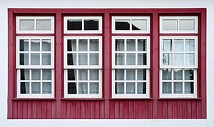 Four Windows With White Trim Set In A Red Wooden Wall Each Has Rectangular