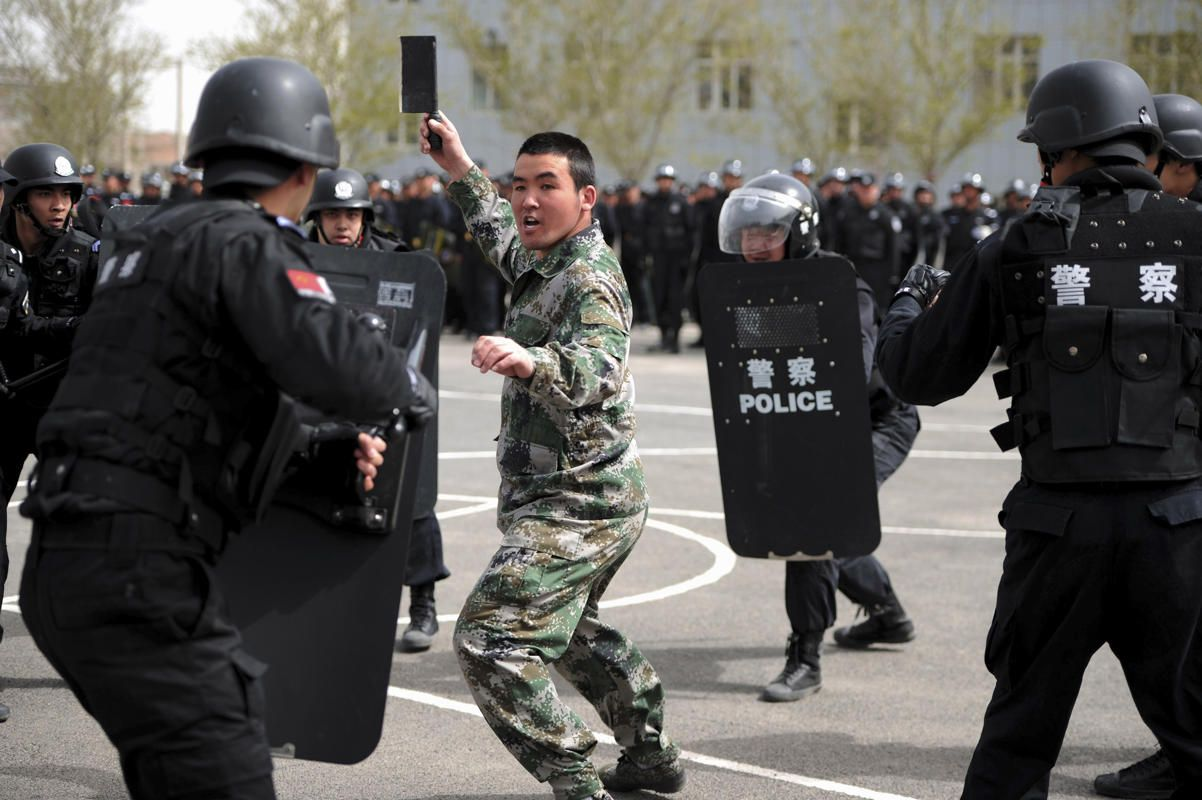 A participant playing the role of an attacker is surrounded by riot policemen during a security drill in Urumqi, Xinjiang Uighur Region April 26, 2014.
