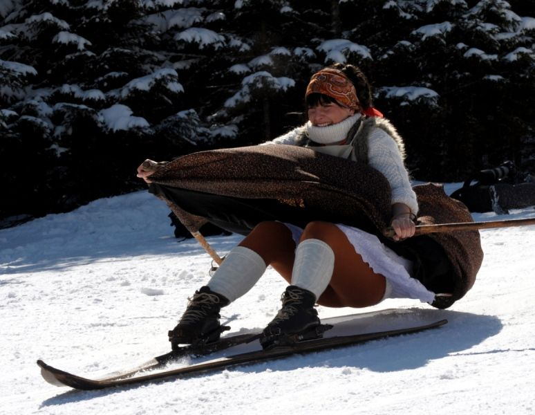 Zakopane, Polen, 9. April 2012:  Carving schaut anders aus: Ein Frau fährt in einem Skifahrer-Outfit aus dem 19. Jahrhundert mit alten Holzskiern in fragwürdiger Haltung einen Hang hinunter. Am Ostermontag findet wie jedes Jahr unweit der polnischen Stadt Zakopane in der hohen Tatra ein Nostalgie-Skirennen statt, das die gute alte Zeit wieder aufleben lässt.