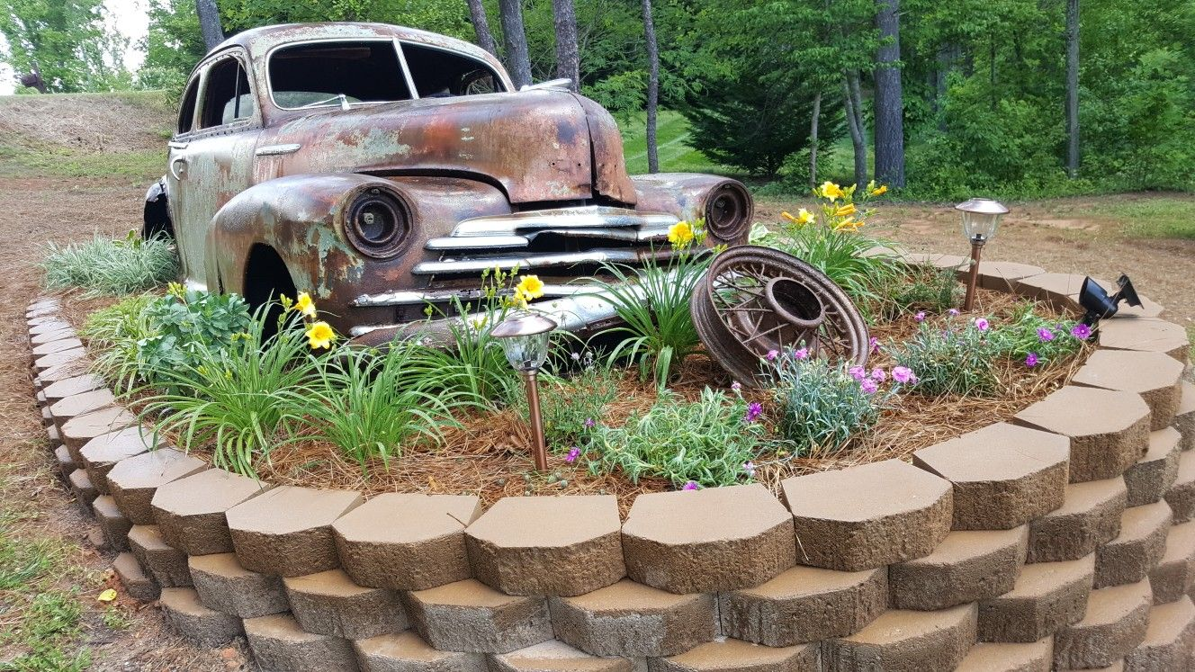 antique car lawn art in landscaping