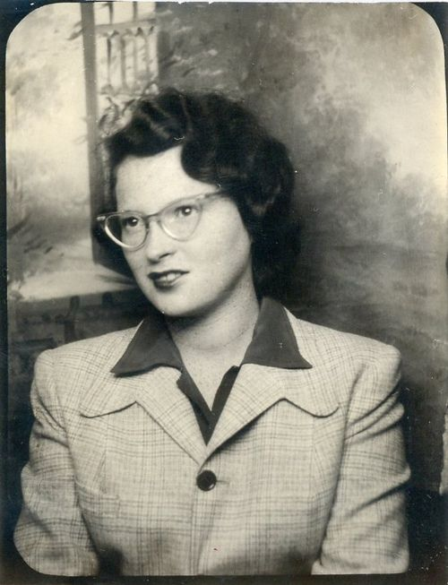 f2b53dad52 An eyeglasses wearing 1940s woman photographed against a painted backdrop.   vintage  glasses  1940s
