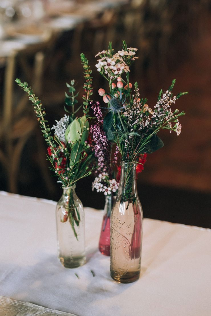 Rustic wildflower wedding centrepiece in mixed vintage bottles | Raconteur Photography