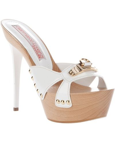 White leather sandal from Gianmarco Lorenzi featuring an open toe, a white front strap with a silver-tone buckle detail and silver-tone studding at the sides, a large wooden platform and a white stiletto heel.