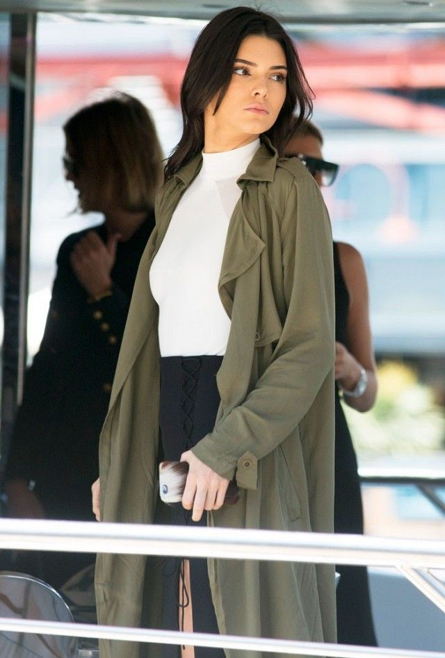 Kendall Jenner wears a white turtleneck and an olive green trench with high waisted black pants.