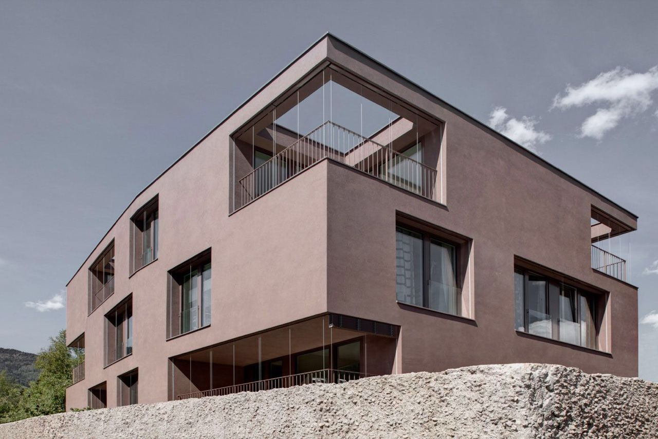 Designed by Bolzana-based firm Pedevilla Architects, 'Pfarrmesnerhaus' is located in Sterzing, the highest city in the alps region (948 meters above sea level). Coated in a dusty pink shade called 'porphyry red', the hue of this apartment block derives from local stone found in the area.