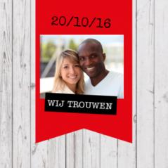 Stoere drieluik trouwkaart met steigerhouten achtergrond en op de voorkant een groot rood vaandel met foto, op de 2e pagina een krijtbord met datum en op de 3e pagina weer een vaandel met de uitnodiging.