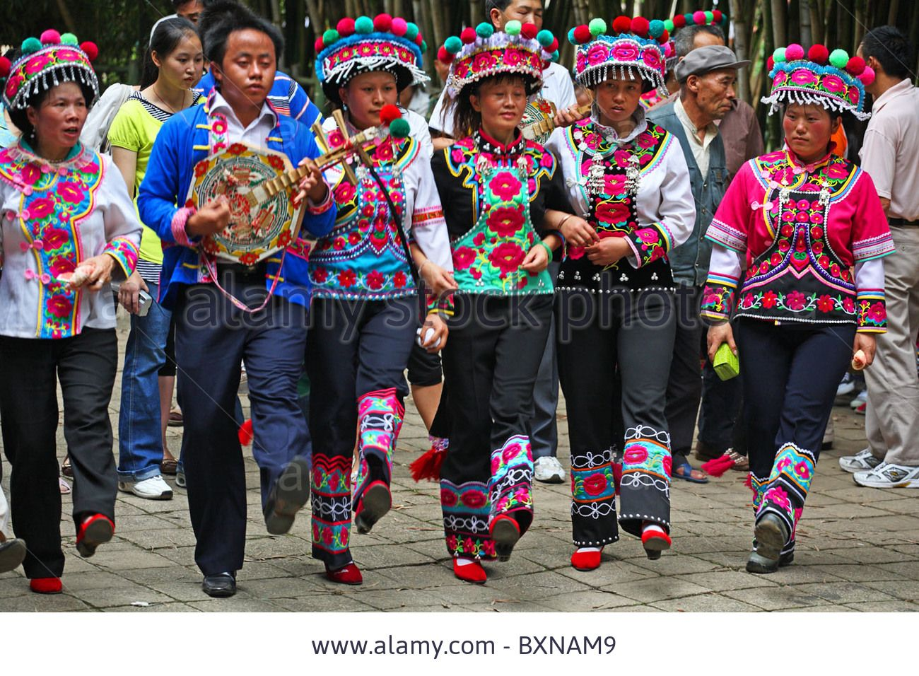 Locals wearing national dress perform in park, Kunming, China Stock Photo