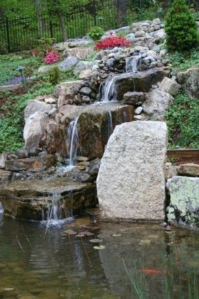 A backyard garden waterfall flows down several tiers of rock