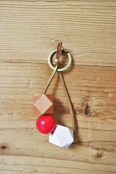 """Schlüsselanhänger (erhätlich für 8,90 €) mit verschiedenen Holzperlen in den Farben kupfer, karminrot und weiß, aufgefädelt auf ein gold-braunes Wildlederband. Der Schlüsselring ist in der Farbe """"Bronze"""". Die Holzperlen wurden von mir mit Acrylfarbe bemalt und anschließend matt lackiert.  Du suchst nach einem Gastgeschenk, z.B. für deine Hochzeit, oder nach Kundengeschenken? Gerne biete ich den Schlüsselanhänger in einer größeren Stückzahl an, andere Farb- bzw. Perlenkombinationen sind…"""