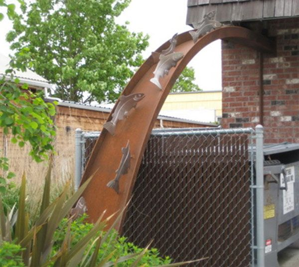 A Beautiful Piece Of Metal Artwork Adds A Very Amusing Touch To The Downspout Yard Drainage Decorative Downspouts Rain Garden