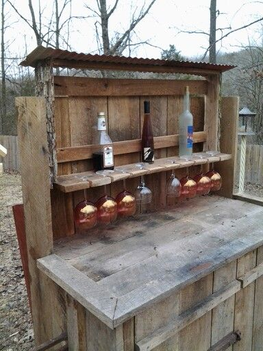 Rustic Wine n Glass Rack attached to outdoor patio bar. Both items made of reclaimed barnwood, pinoak logs and old tin roof. Wine rack is removable and can be attached as a wall hanging.