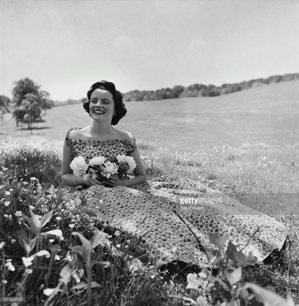 Debutante Elizabeth Guest, in a sleeveless, printed organdy dress by Simonetta, sitting in a meadow with flowers in her hand.