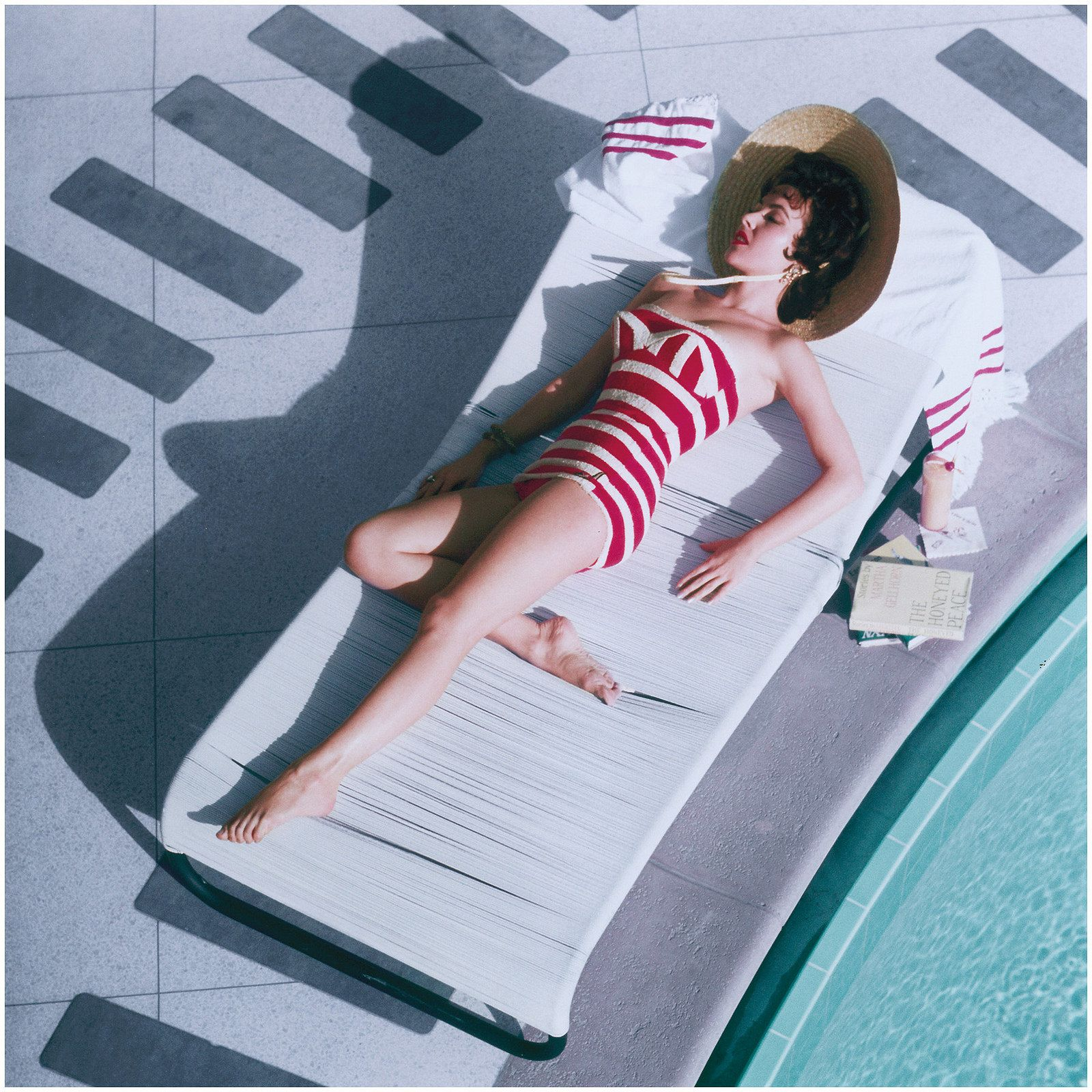 Austrian actress Mara Lane lounging by the pool in a red and white striped bathing costume at the Sands Hotel, Las Vegas, 1954. (Photo by Slim Aarons/Hulton Archive/Getty Images)