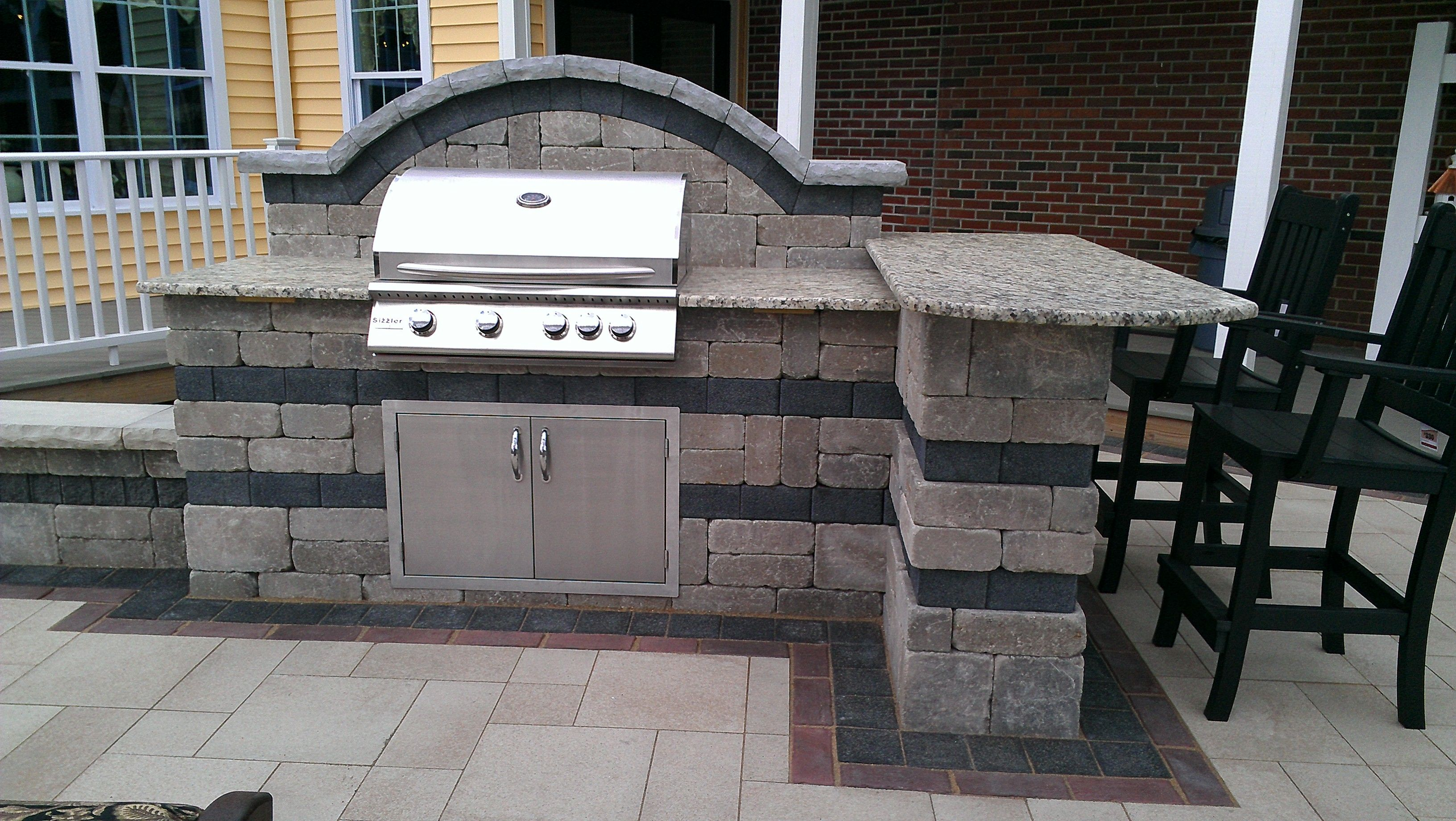 Outdoor Kitchen and Bar with Stainless steel grill and doors on a