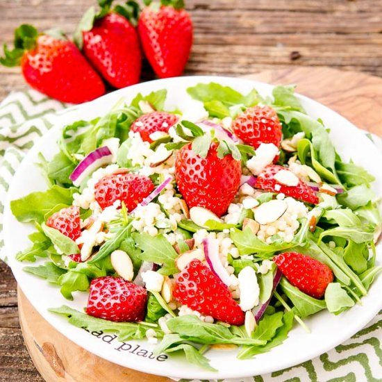Sparkling Strawberry Salad is a delightful mix of arugula, fruit, nuts, cheese, and homemade dressing.