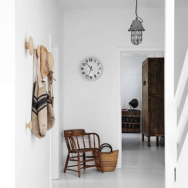 An HK Living lamp and a clock from Sanders & King Interiors in the hall, looking towards a Chinese cupboard in the sitting room. From one of our most popular summer stories, 'pared-back Aussie coastal home'. Photography @sharyncairns, styling @carolewhiting #hallway #interiordesign