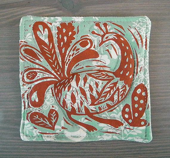 Set of 4 block printed & quilted fabric coasters on patterned pale teal fabric. They feature a peacock design.