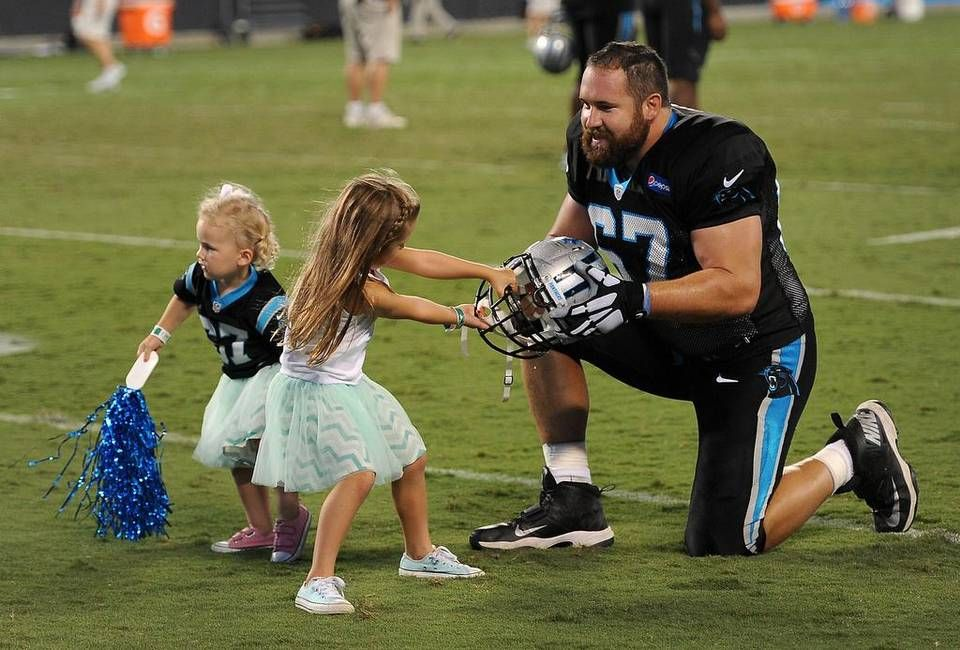 Carolina Panthers center Ryan Kalil, right, plays tug of war with his helmet with his daughter, Kenadi, 4 yrs., as Chandler Kalil, 2 yrs., plays following Fan Fest at Bank of America Stadium on Friday, August 7, 2015.
