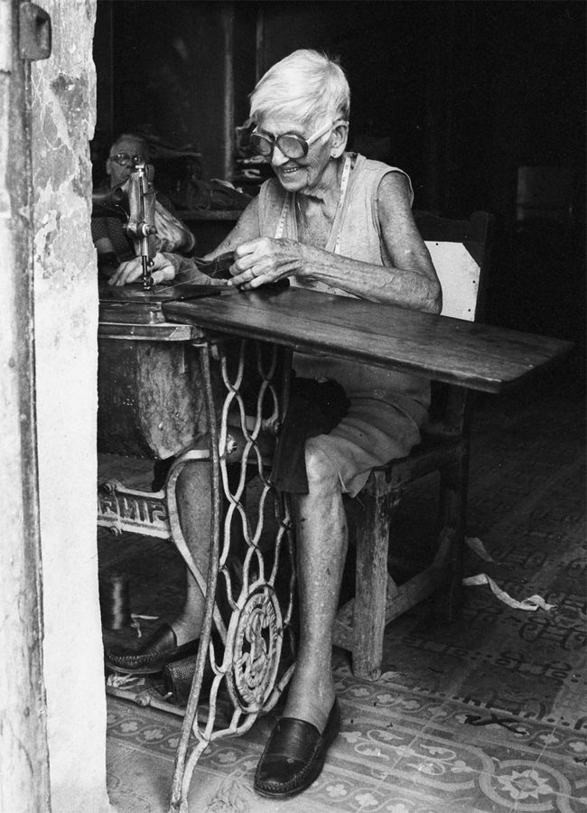 Havana. (If you can't make it to Cuba, try Tampa's Ybor City --the old Cuban section where you can watch 'em hand roll cigars). This woman is sewing though (a surprisingly valuable skill for sailors and islanders).