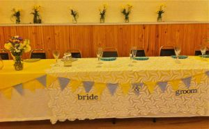 Head table bride and groom blue and yellow bunting.