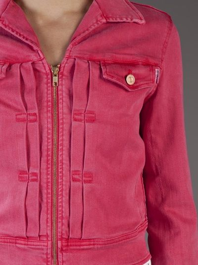 Crop denim jacket in pink from Mother. Features a collar with exposed zipper closure, two front flap pockets with button closure and pleated front panels.