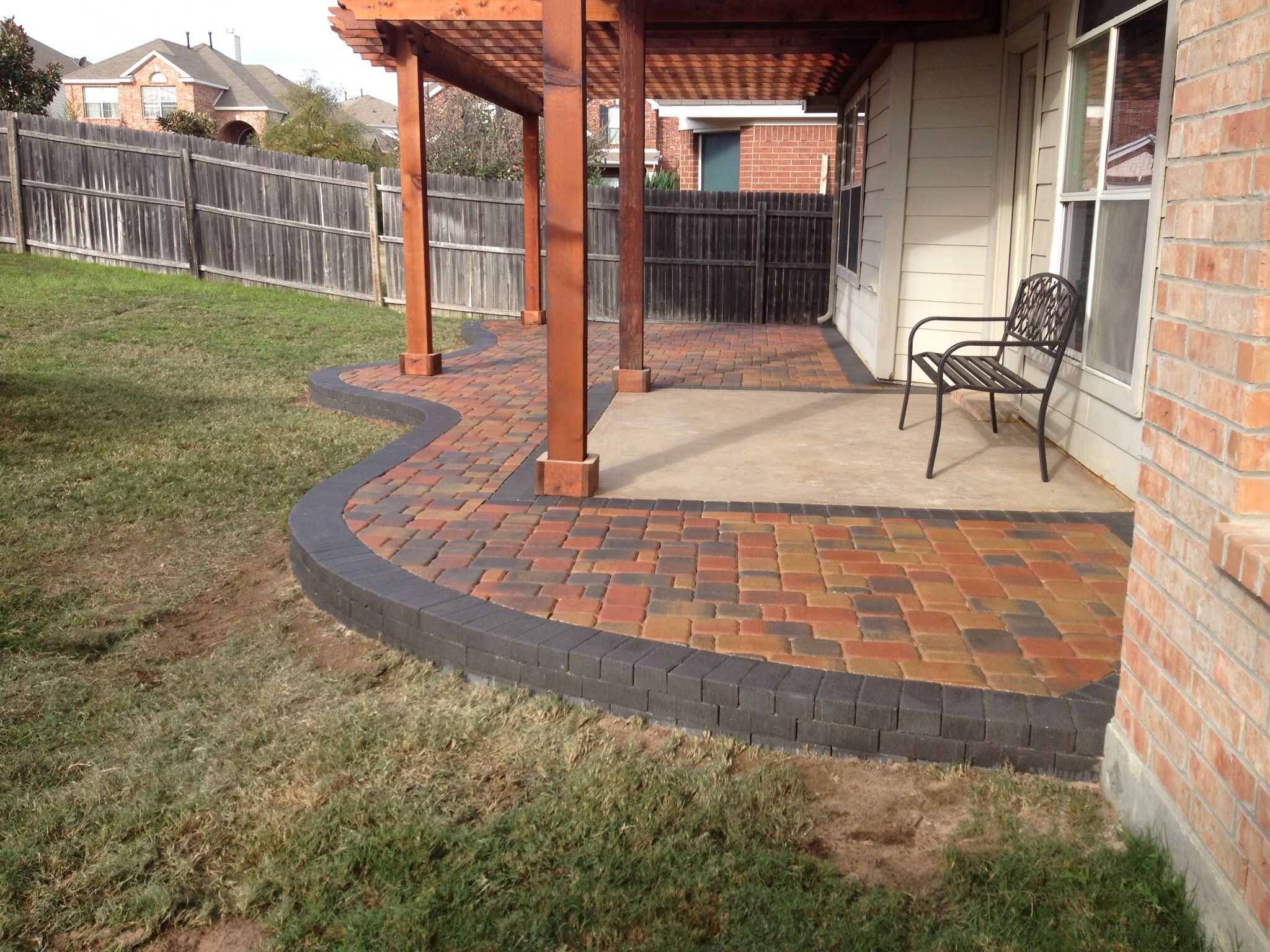 multicolored paver patio installed around an existing concrete