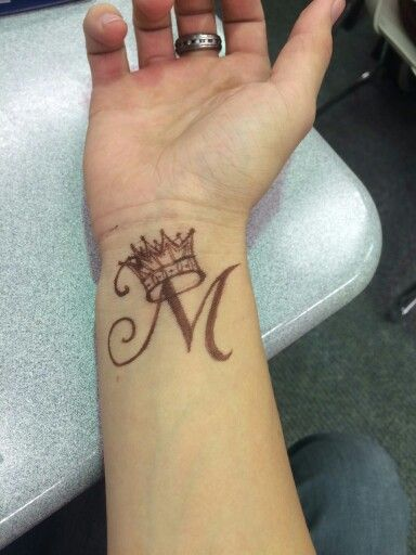wrist tattoo letter m with a crown crown means self