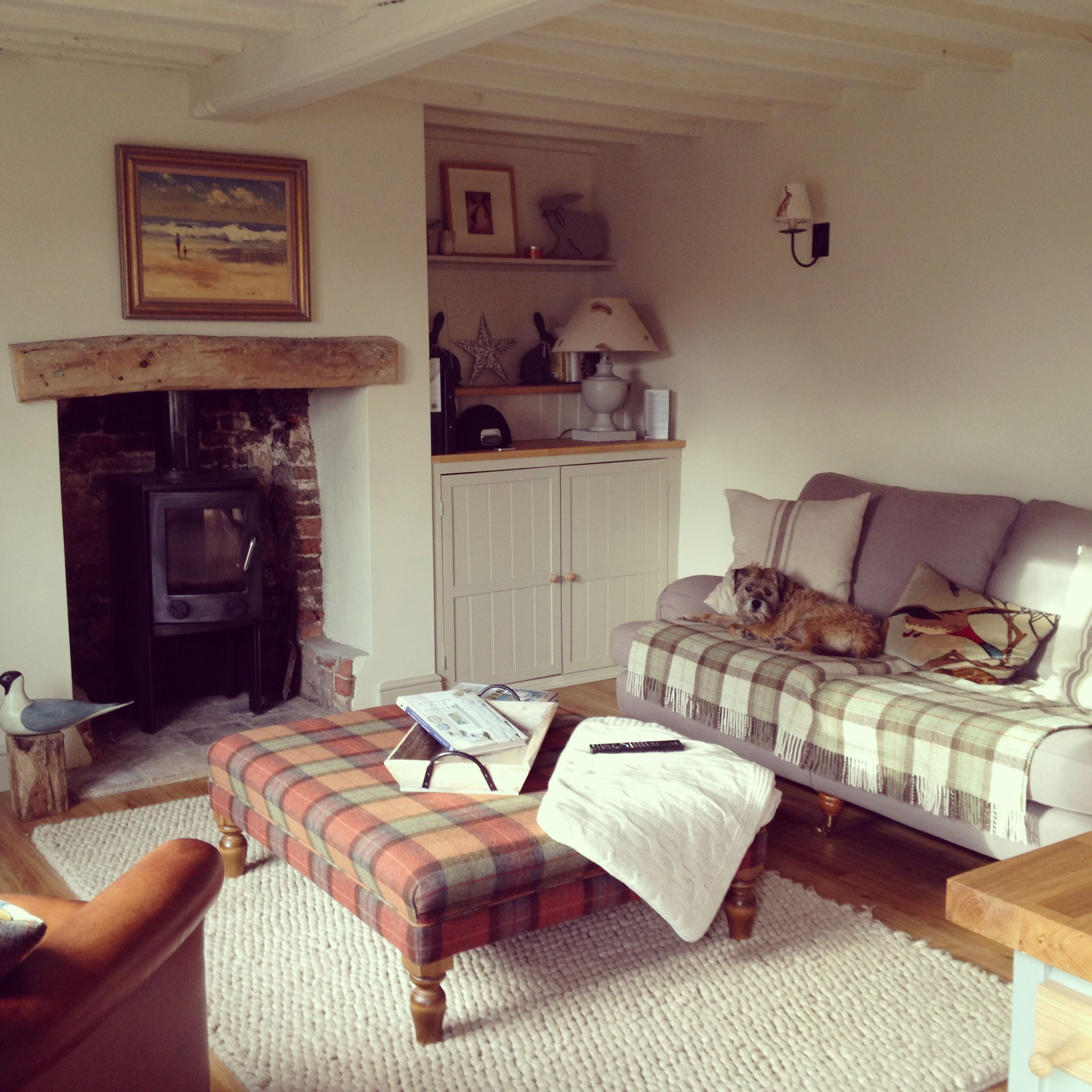 Cosy cottage living room. Checked armchair and footstool with ...